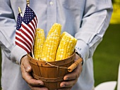 Man holding woodchip basket full of corn cobs with US flags