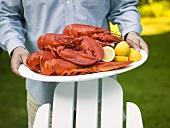 Man serving lobsters with lemons on platter (USA)
