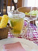 Laid table with corn cobs, drink and salad (USA)