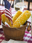 Corn cobs with American flag on laid table (USA)
