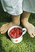 Raspberries in a mug on grass between a child's feet