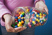 Hand tipping bubblegum balls out of storage jar