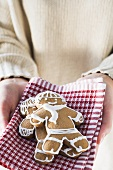 Hands holding two gingerbread men on tea towel