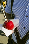 Man in national dress holding toffee apple (Oktoberfest, Munich)