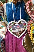 Woman in national dress with Lebkuchen heart (Oktoberfest, Munich)