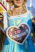 Girl with Lebkuchen heart at Oktoberfest in Munich