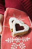 A hand holding jam biscuits in a Christmassy cloth