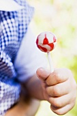 Child's hand holding a lollipop