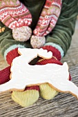 Child's hands in woollen mittens holding gingerbread reindeer