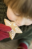Child biting into gingerbread star