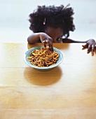 Small girl reaching for spaghetti bolognese
