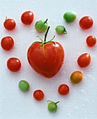 Heart-shaped tomato surrounded by cherry tomatoes