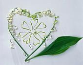 Herz aus Blüten und Blatt von Maiglöckchen auf weißem Papier