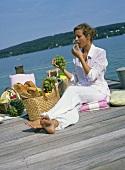 Woman eating grapes at lakeside picnic
