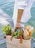 Woman with full picnic bag at lakeside