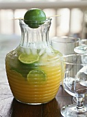 Lemonade with slices of lime in a glass jug