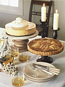 Cheesecake, pear tart and brandy on laid table
