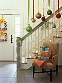 Geschenke auf Polsterstuhl neben Treppenaufgang auf weihnachtlich dekoriertem Flur