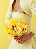 Bride holding bouquet of yellow roses and orchids