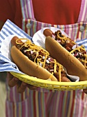 Hands holding two hot dogs with mince sauce and cheese