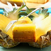 Piece of pineapple cake on two pineapple halves