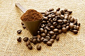 Ground coffee in measuring spoon and coffee beans on jute