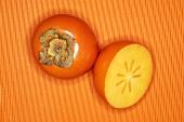 Sharon fruits, whole and half, on orange background