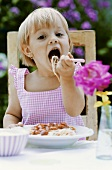 Small girl eating spaghetti in open air