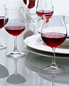 Table with red wine glasses and plates