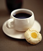 A cup of coffee with ginger biscuits