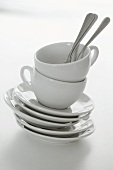 White coffee cups with saucers and spoons