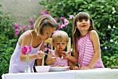 Three girls eating spaghetti in open air