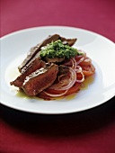 Rump steak with pesto on onions and tomatoes