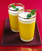 Two glasses of mango lassi (Indian mango & yoghurt drink)