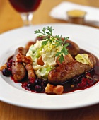 Sausages with mashed potato, bacon and blueberry sauce