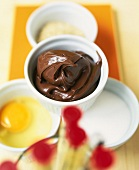 Soufflé dish with chocolate spread and baking ingredients