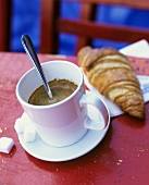 A cup of espresso with croissant
