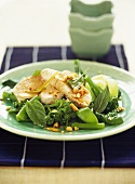 Poached chicken breast on a bed of green vegetables