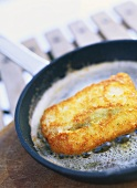Frying breaded cod in frying pan