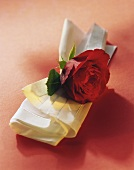 White fabric napkin with red rose