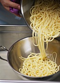 Putting cooked spaghetti into a sieve