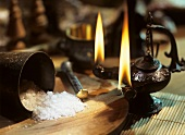 Coarse sea salt with mortar and oil lamp