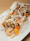 Mixed seafood in clingfilm on crushed ice