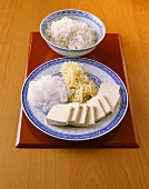 Ingredients for Asian fondue: tofu, glass- & rice noodles, rice