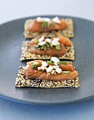 Raw salmon fillet on sesame crispbread