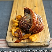 Roast pork with crackling, with potatoes on wooden board