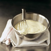 Bowl of whipped cream with whisk