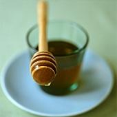 Glass of honey with honey dipper
