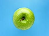 A Granny Smith apple with drops of water