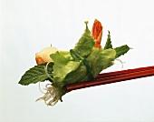 Lettuce leaf with shrimp and rice noodles on chopsticks